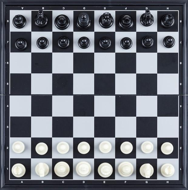 La strategia e il concetto di scacchi con scacchi dipendono la vista superiore della scacchiera. Foto Gratuite