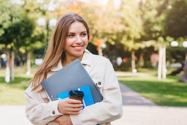 La studentessa bionda cammina nel parco con i taccuini delle cartelle e una tazza di caffè Foto Premium