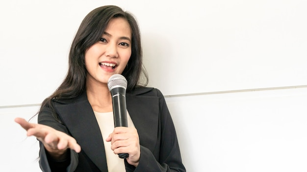 La suite da portare asiatica felice della donna di affari sta parlando con il microfono e sta presentando al pubblico. Foto Premium