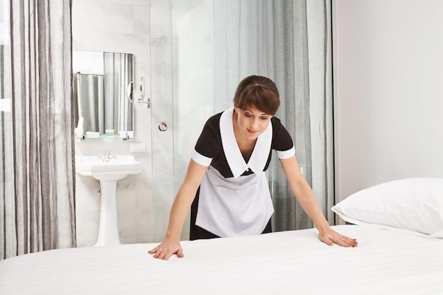 La superficie del letto deve essere pulita e ordinata. colpo dell'interno della donna che indossa l'uniforme della domestica, facendo il letto e sorridendo, essendo di buon umore mentre lavora nell'hotel come domestica. stanza di pulizia dei dipendenti del suo datore di lavoro Foto Gratuite