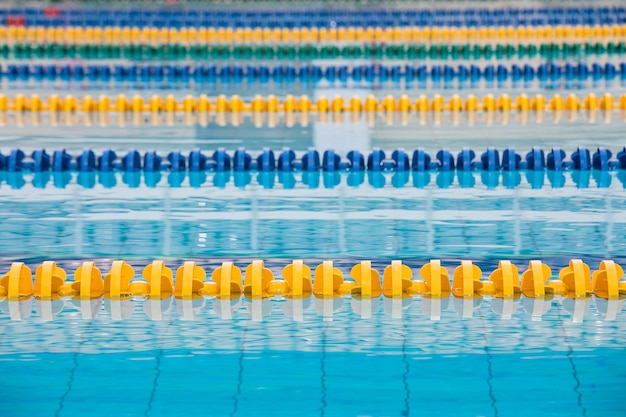 La superficie della piscina con acqua blu e divisori gialli e blu di piste di nuoto Foto Premium