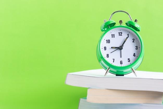 La sveglia verde si trova sulla pila di libri con sfondo verde Foto Premium