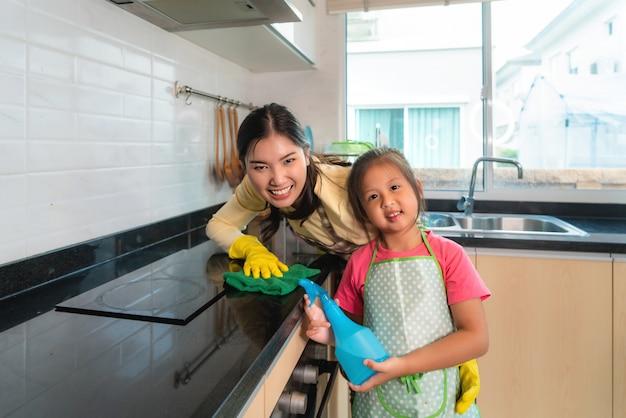 La tavola allegra asiatica di pulizia della figlia e della madre sorge con lo straccio e la bottiglia dello spruzzo insieme al contatore di cucina in casa. Foto Premium
