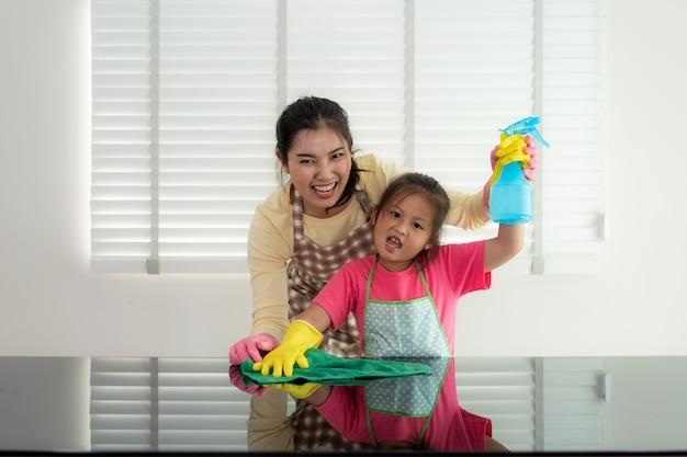 La tavola allegra asiatica di pulizia della figlia e della madre sorge con lo straccio e la bottiglia dello spruzzo insieme Foto Premium