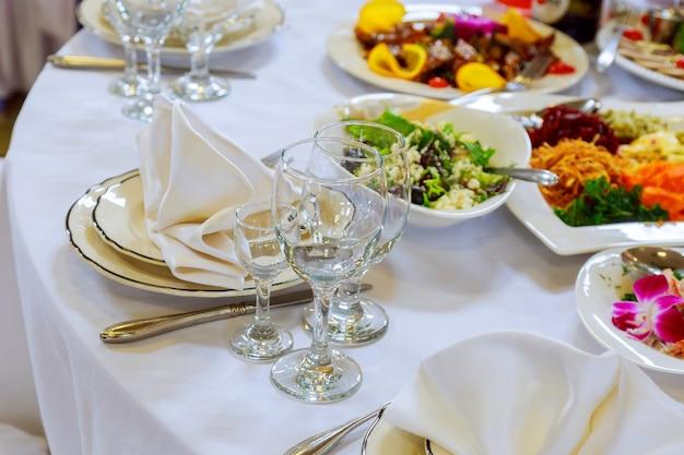 La tavola meravigliosamente decorata ha messo con i fiori, le candele, l'evento dei piatti nel ristorante Foto Premium