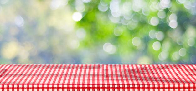 La tavola vuota con la tovaglia rossa sopra l'albero di verde della sfuocatura ed il fondo del bokeh, per alimento e prodotto visualizzano il fondo del montaggio, insegna Foto Premium