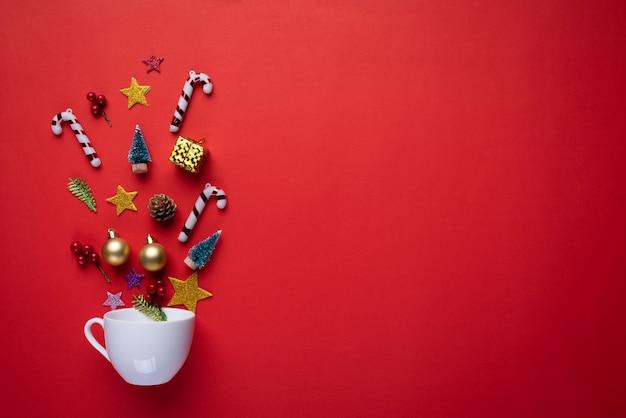 La tazza bianca spruzza la decorazione di natale su priorità bassa rossa. Foto Premium