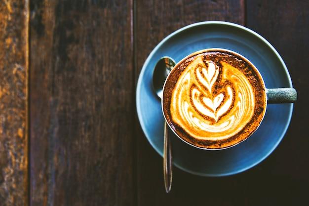 La tazza di cappuccino caldo è sul tavolo di legno Foto Premium