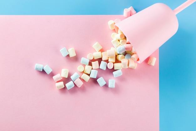 La tazza ha riempito di caramelle gommosa e molle sulla superficie di carta rosa Foto Gratuite