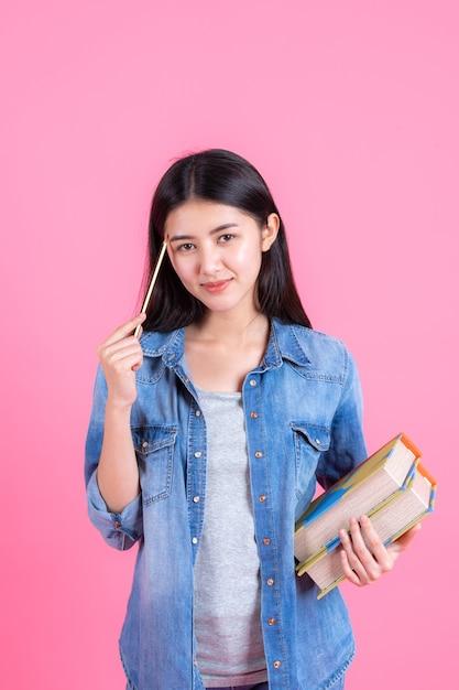 La tenuta femminile abbastanza adolescente del ritratto prenota in suo braccio e usando la matita sul rosa Foto Gratuite