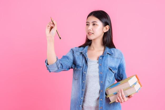 La tenuta femminile adolescente prenota in armi e usa la matita Foto Gratuite