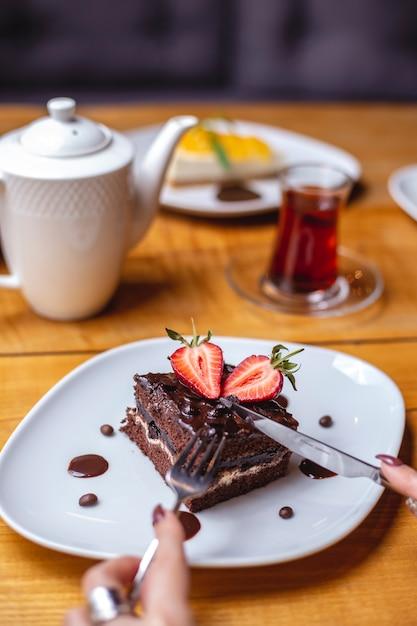 La torta al cioccolato con vista laterale con scaglie di cioccolato crema alla fragola aggiungono tè nero sul tavolo Foto Gratuite