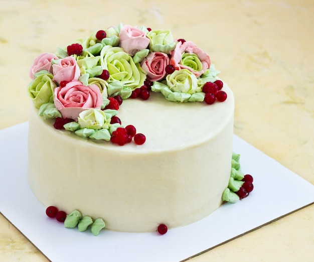 La torta di compleanno con i fiori è aumentato su luce Foto Premium