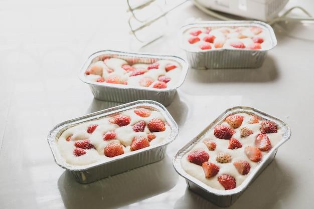 La torta di fragole nel vassoio di alluminio è pronta per la cottura. Foto Premium
