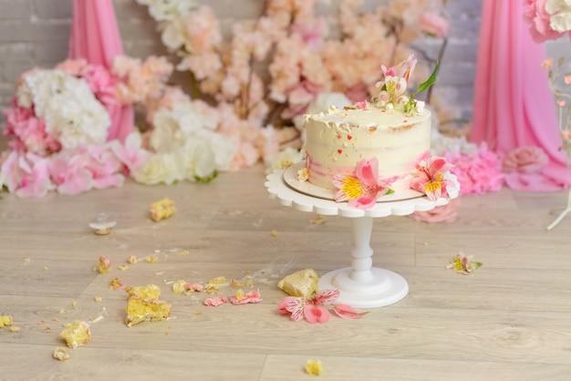 La torta distrutta con crema bianca e rosa per un compleanno dell'età bambino di un anno Foto Premium