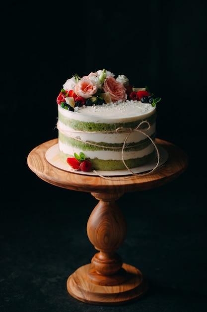 La torta è decorata con fiori su un buio. Foto Premium