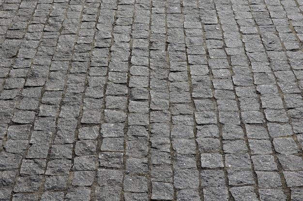 La trama della lastra di pavimentazione (pietre per lastricati) di molte piccole pietre di forma quadrata sotto la luce del sole Foto Premium