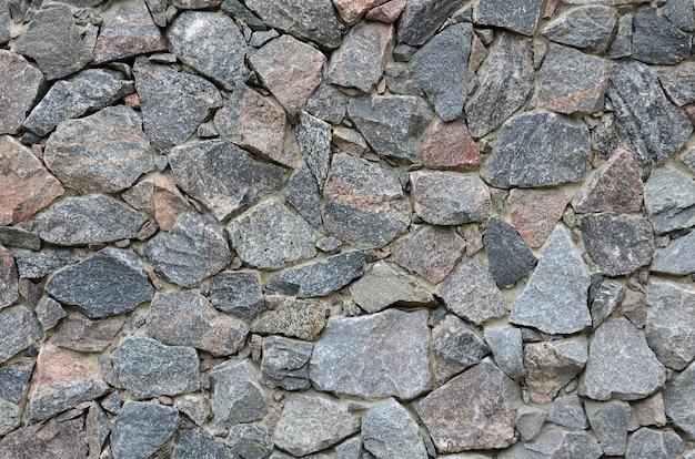 La trama di un forte muro di pietra di molte pietre concrezionate di varie forme Foto Premium