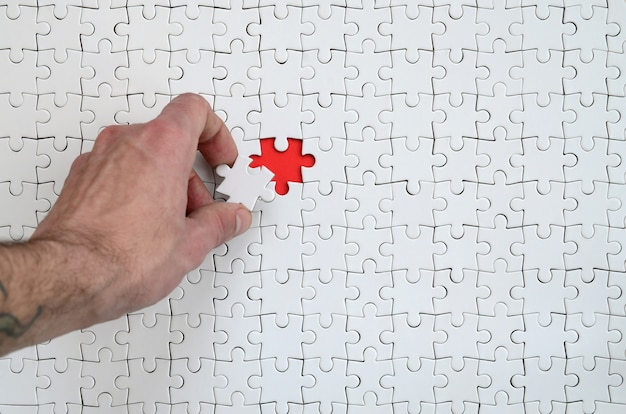 La trama di un puzzle puzzle bianco nello stato assemblato con un elemento mancante che la mano maschile inserisce Foto Premium