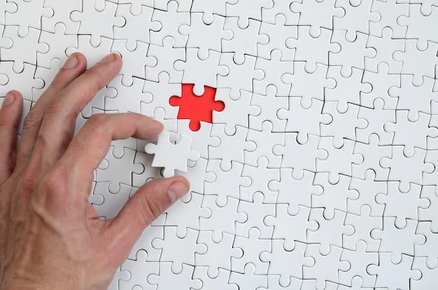 La trama di un puzzle puzzle bianco nello stato assemblato con un elemento mancante Foto Premium