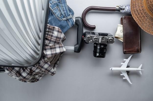 La valigia grigia ha imballato per il viaggio con l'aeroplano minimo, i vestiti e gli accessori - concetto di viaggio Foto Premium