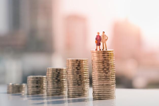 La vecchia figura delle coppie che si leva in piedi in cima alla pila di moneta. Foto Premium
