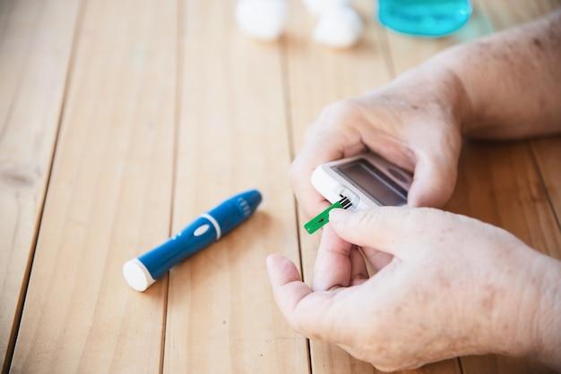 La vecchia signora sta testando il livello di zucchero nel sangue usando il set di test per zucchero nel sangue Foto Gratuite