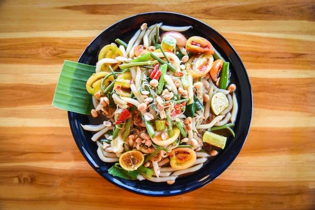 La verdura e l'arachide della tagliatella della miscela dell'insalata della papaia sono servito sull'alimento tailandese piccante dell'insalata della tagliatella di riso della tavola Foto Premium
