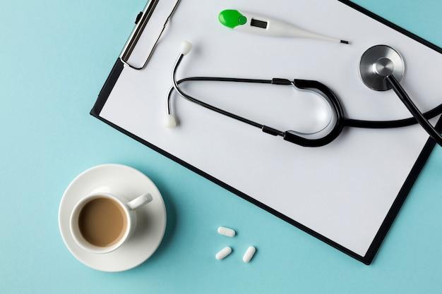 La vista dell'angolo alto degli strumenti e delle medicine di sanità si avvicina al blocco note a spirale e al computer portatile sopra lo scrittorio Foto Gratuite