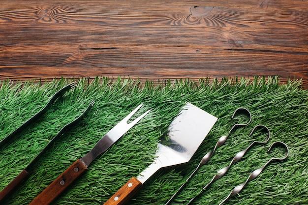 La vista dell'angolo alto dell'utensile del barbecue ha messo sulla stuoia verde sopra la tavola di legno Foto Gratuite