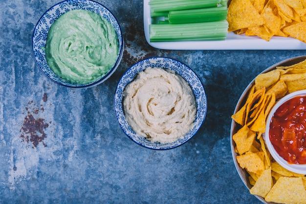 La vista elevata dei chip messicani dei nachos con guacamole e salsa sauce in ciotola Foto Gratuite