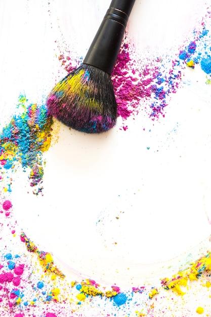La vista elevata di compone la spazzola e la polvere compatta variopinta su fondo bianco Foto Gratuite