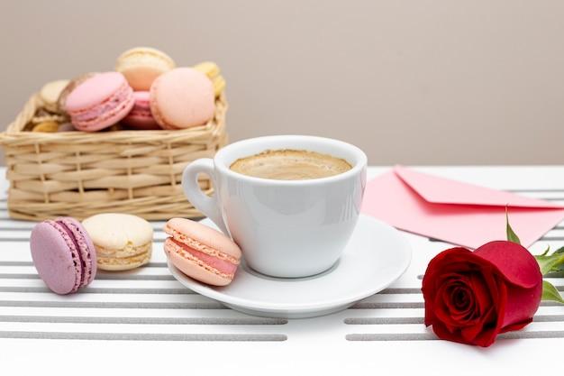 La vista frontale della tazza di caffè con è aumentato per il giorno di biglietti di s. valentino Foto Gratuite