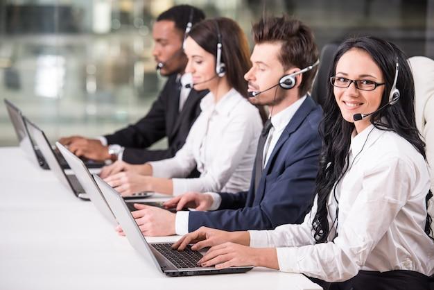 La vista laterale della linea di impiegati del call center sta sorridendo. Foto Premium