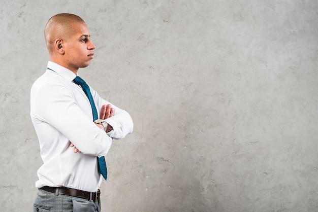 La vista laterale di giovane uomo d'affari con le sue braccia ha attraversato la condizione contro la parete grigia Foto Gratuite