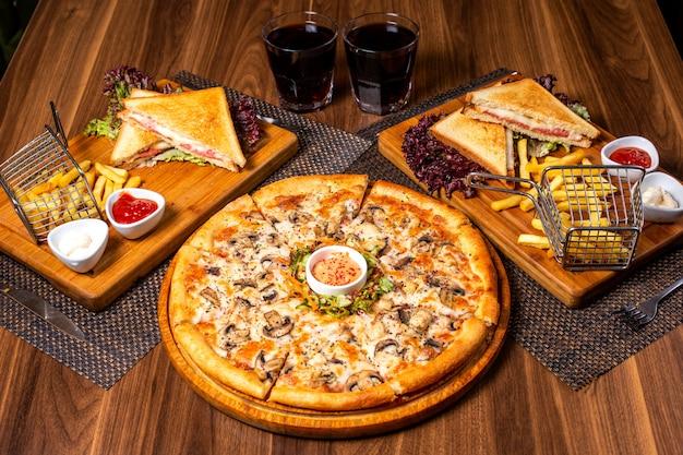 La vista laterale di pizza con il pollo ed i funghi è servito con insalata delle verdure e della salsa sul piatto di legno Foto Gratuite