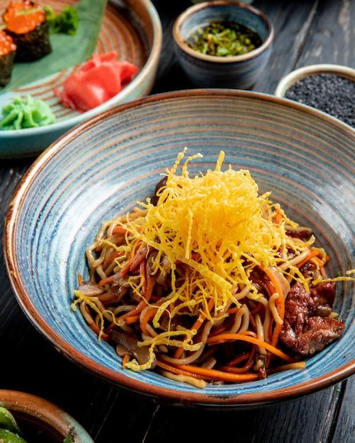 La vista laterale di scalpore ha fritto le tagliatelle con manzo e le verdure in un piatto sulla tavola di legno Foto Gratuite
