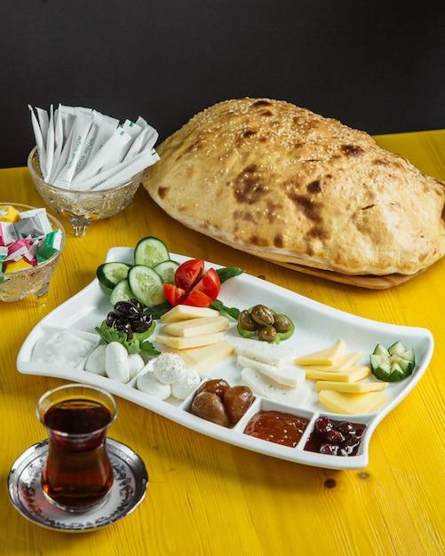 La vista laterale di un piatto con l'alimento di prima colazione con il miele e la marmellata del formaggio delle olive degli ortaggi freschi è servito con tè Foto Gratuite