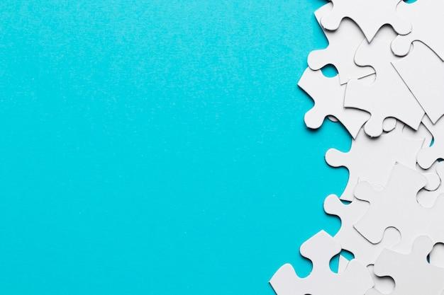 La vista sopraelevata di molti pezzi bianchi del puzzle su superficie blu Foto Gratuite