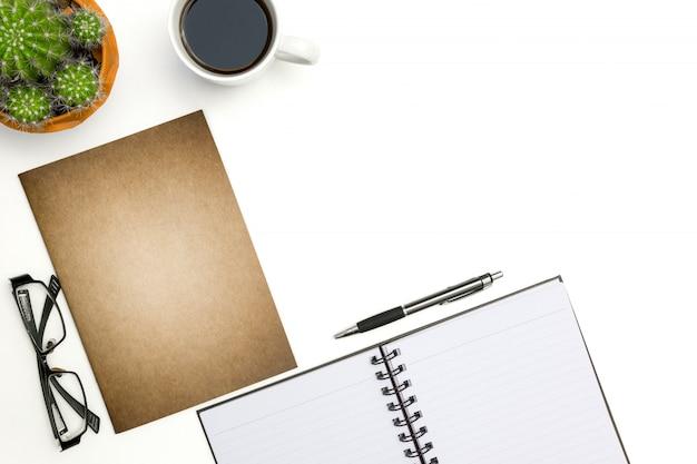 La vista superiore apre il taccuino, la penna ed il cactus sul fondo bianco dello scrittorio Foto Premium
