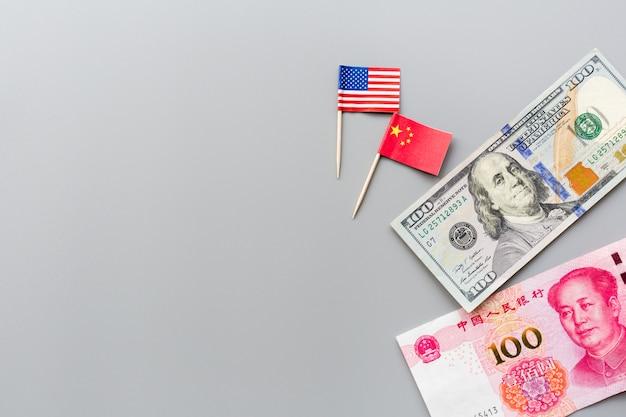 La vista superiore creativa pone la disposizione delle bandiere di usa e cina e dollaro americano del denaro contante Foto Premium