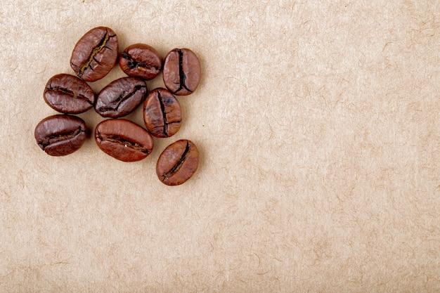 La vista superiore dei chicchi di caffè arrostiti ha isolato il fondo di struttura della carta marrone con lo spazio della copia Foto Gratuite
