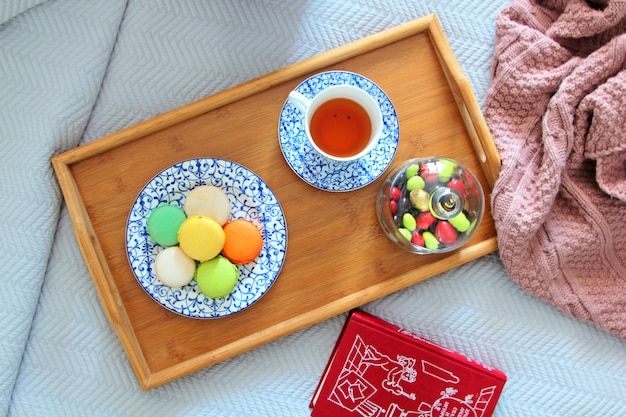 La vista superiore dei maccheroni su un piatto è servito con tè su un vassoio di legno Foto Gratuite