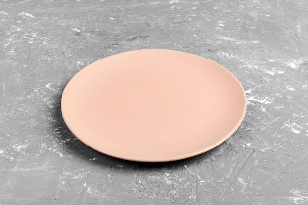 La vista superiore del piatto rosa vuoto rotondo opaco sullo spazio scuro della copia del fondo del cemento per voi progetta. Foto Premium