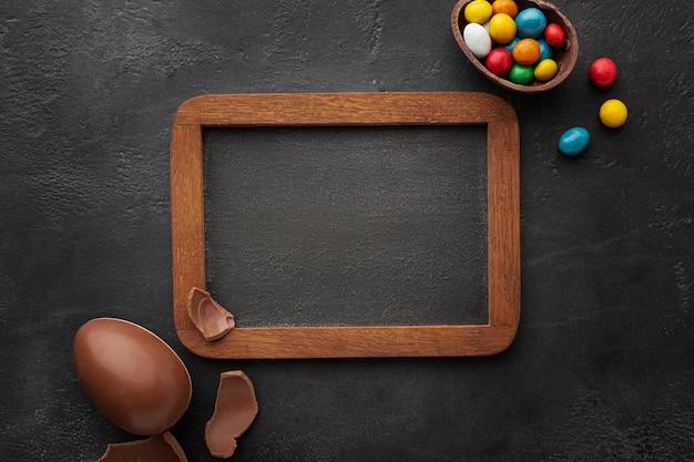 La vista superiore della lavagna con le uova di pasqua del cioccolato ha riempito di caramella variopinta Foto Gratuite