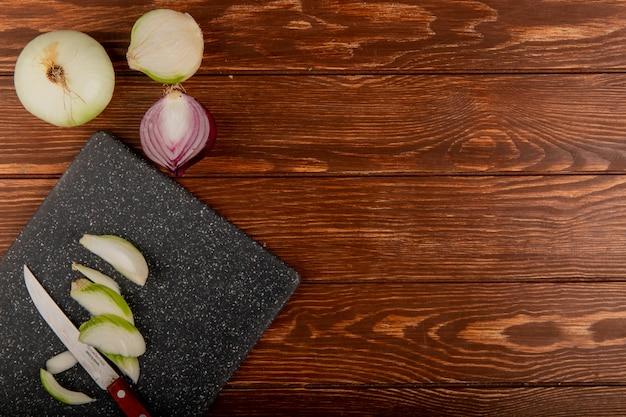 La vista superiore delle fette e del coltello della cipolla bianca sul tagliere con interi e mezzo ha tagliato la cipolla rossa su fondo di legno con lo spazio della copia Foto Gratuite