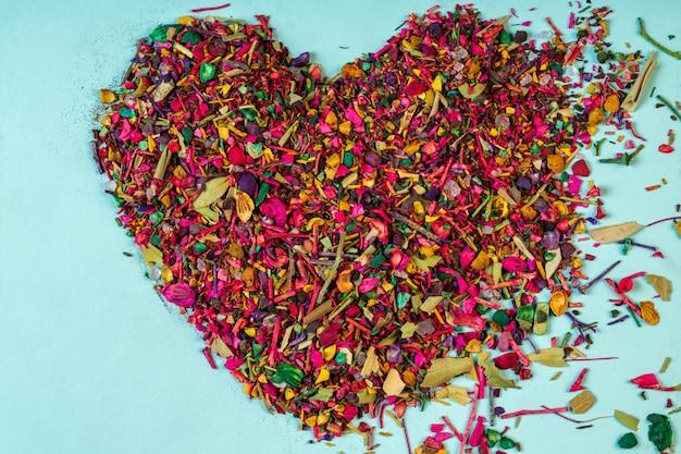 La vista superiore delle fioriture e delle erbe multicolori dei petali del fiore secco ha sistemato a forma di cuore sul blu Foto Gratuite