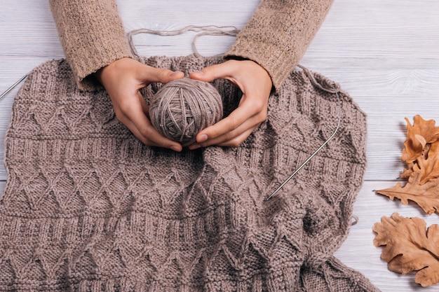 La vista superiore delle mani di una donna che tengono una palla di filato di lana nei precedenti tricotta il maglione Foto Premium