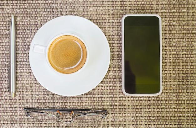 La vista superiore di caffè con i vetri della penna ed il telefono cellulare sopra tessono il fondo di bambù Foto Gratuite