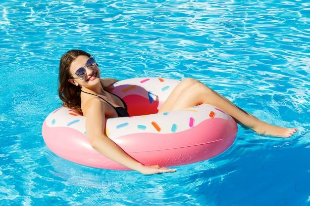 La vista superiore di giovane femmina nuota con il cerchio rosa in stagno Foto Premium